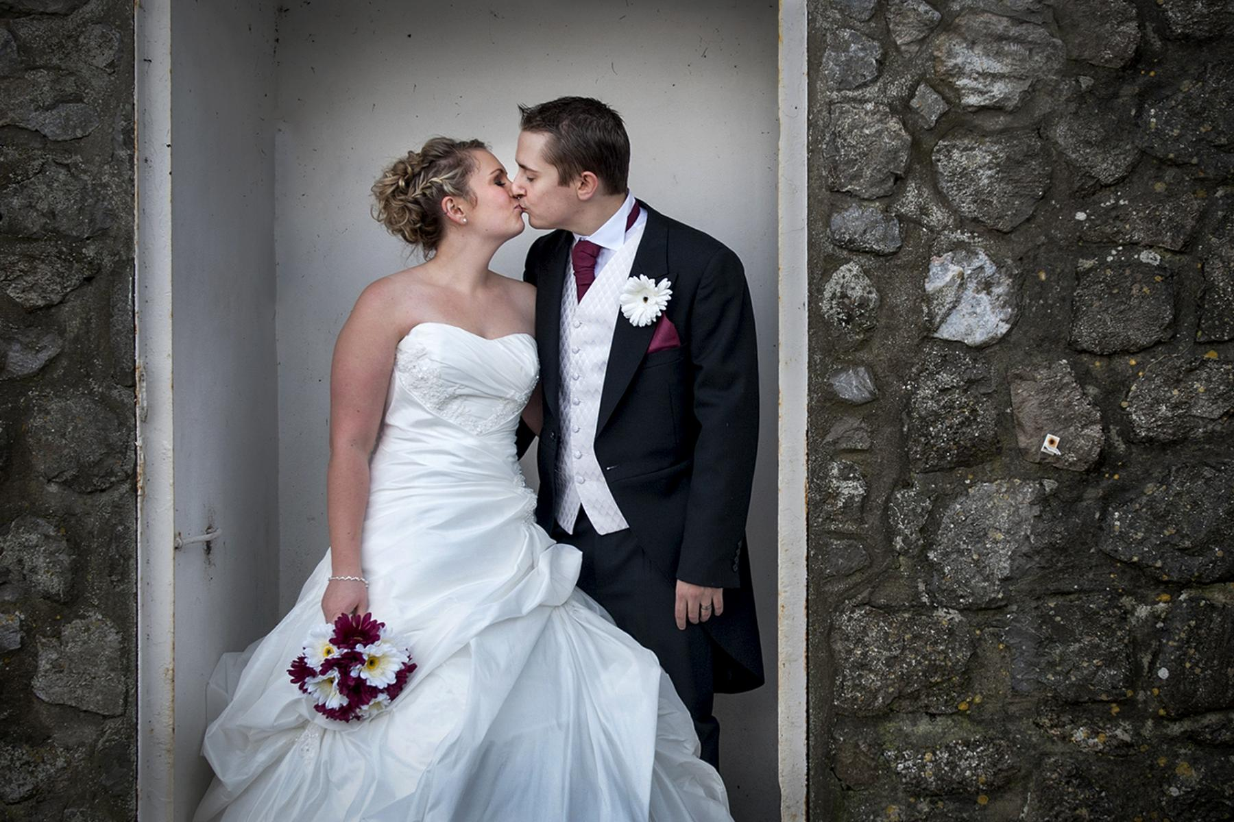 Oxwich-Bay-wedding-photography-newly-married-couple-kissing-white-doorway