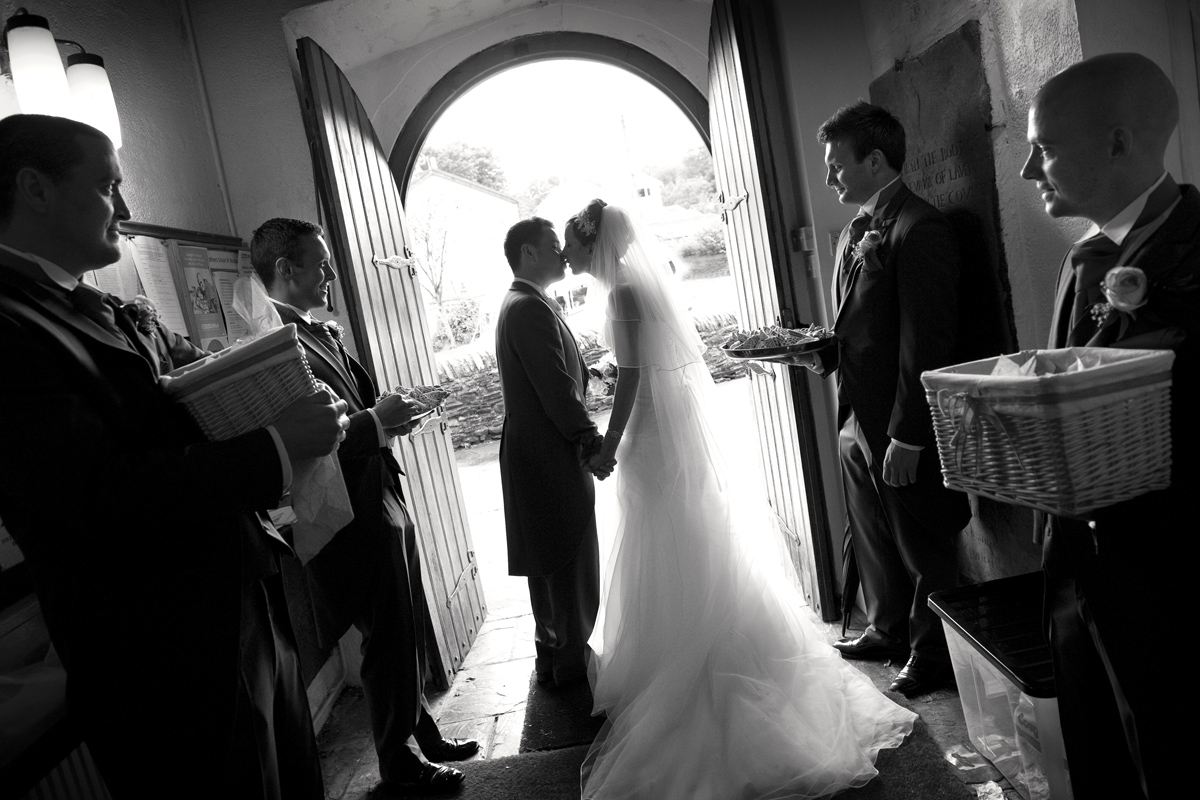 Bride-groom-kissing-doorway-st Illtud's-church=wedding-photographer