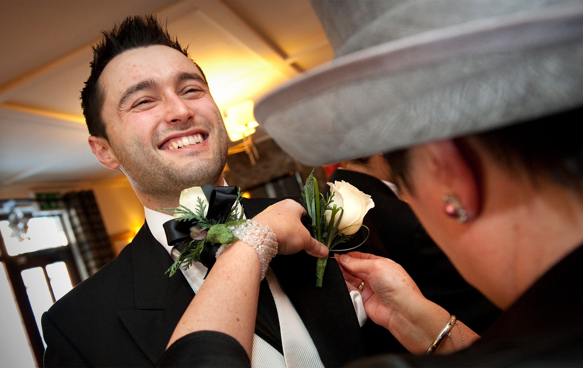 Bridgend-wedding-photography-grooms-mother-attaching-groom's-buttonhole-Pheasant-Inn-Pen-y-Fai